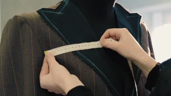 Tailor Taking Measures with Measuring Tape on a Mannequin