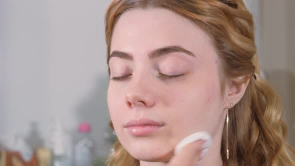 Preparing the Model's Skin for Applying Makeup. Treatment of the Face with a Cotton Pad Dipped in a