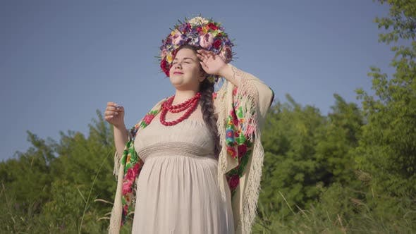 Thumbnail for Portrait of Cute Plump Woman with a Wreath on Her Head Smiling in Sunlight on the Green Summer Field