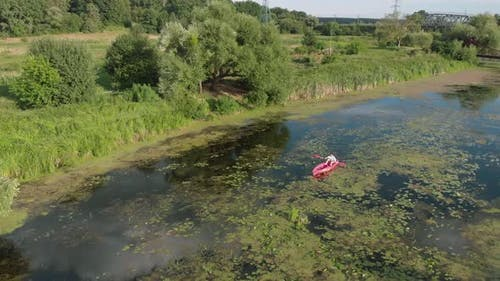 Drone view of woman floating in boat on river. Female is kayaking along beautiful landscape.