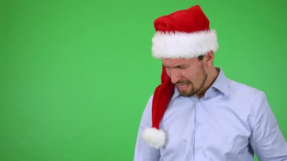 Thumbnail for A Young Handsome Man in a Christmas Hat Cries - Green Screen Studio