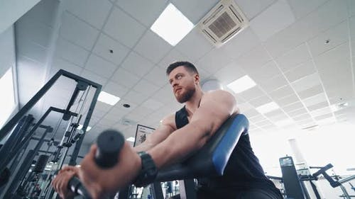 Persistent bodybuilder pumps his arm muscles. Muscular athlete training on a new simulator