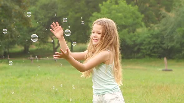 Thumbnail for Cheerful Girl Plays Catch Soap Bubbles on the Meadow. Slow Motion. Close Up