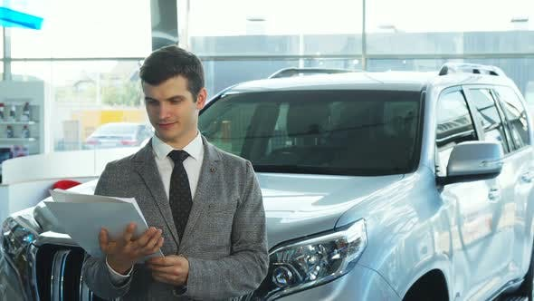 Thumbnail for A Happy Buyer Presents a Car From the Automobile Showroom