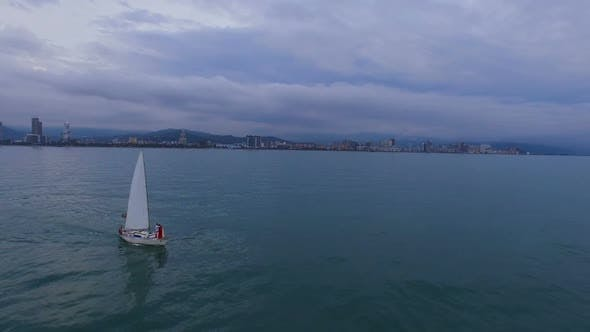 Thumbnail for Couple Standing at Front End of Sailing Boat Swimming Against Batumi City Line