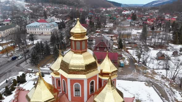 Thumbnail for Aerial View of Ukrainian Church with Golden Domes in Carpathian Village in Winter