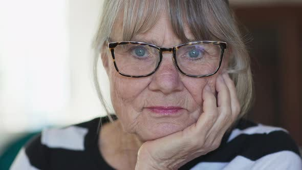 Thumbnail for Portrait of senior white woman with glasses with her chin resting on her hand
