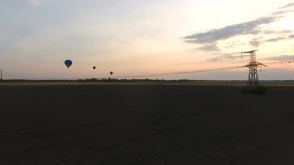 Thumbnail for Air balloons flying over fields at dusk electric cables bellow industrialization