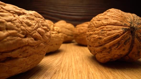 Walnut Close Up on a Wooden Table. Vertical Sliding Camera Moving Through Nut. Laowa Probe Lens.