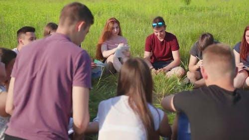 Teamwork von freundlichen Studenten auf dem Rasen