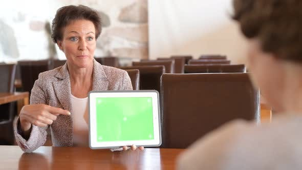 Thumbnail for Happy Mature Businesswoman Showing Digital Tablet While Talking With Senior Woman