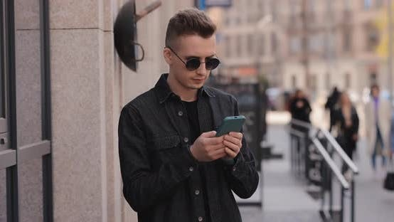 Young Man in Sunglasses Using Phone in a City