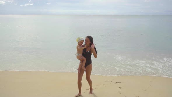 Thumbnail for Mom with a Two-year-old Daughter Walking Along the Sandy Beach