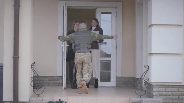 Thumbnail for The Young Soldier in Military Closes Running To His Family, Cuddling His Sisters