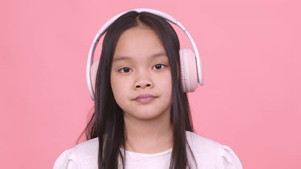Nahaufnahme Porträt eines kleinen asiatischen Mädchens mit großen kabellosen Kopfhörern, rosa Studio-Hintergrund
