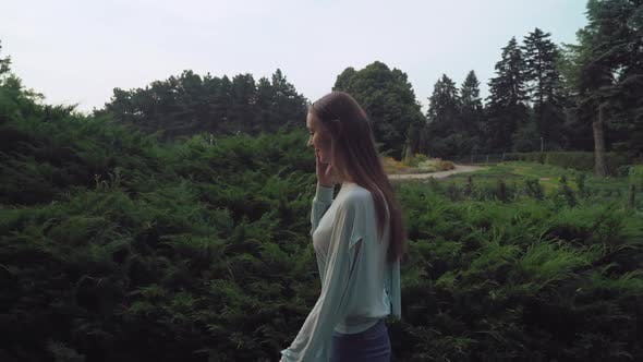 Thumbnail for Young Woman Goes Along the Bushes in the Park and Talking on the Phone