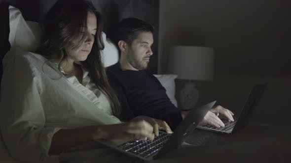 Thumbnail for Young Couple Using Laptops in Bed