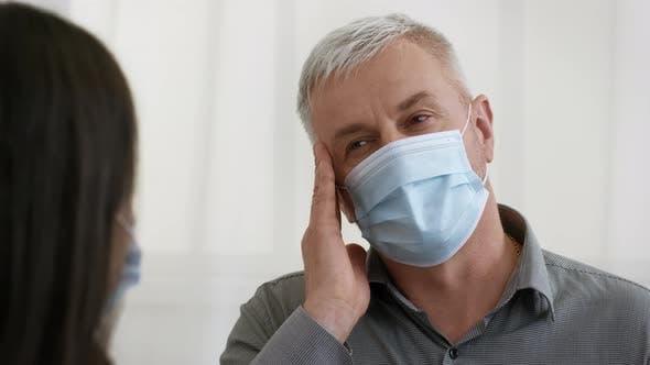 Mature Male Patient Complaining Doctor About Migraine Pain Indoors