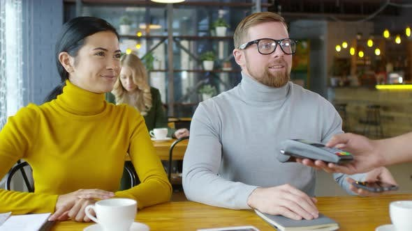 Thumbnail for Cheerful Man Paying with Smartphone on Lunch with Colleague
