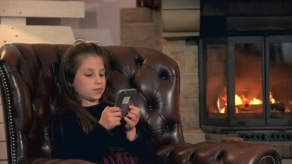 Thumbnail for Little Girl Spend Her Leisure Time with Smartphone Near the Fireplace