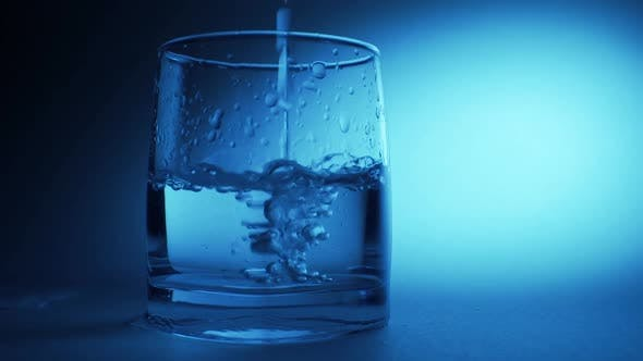 An effervescent soluble tablet falls into a glass of water. On a blue background