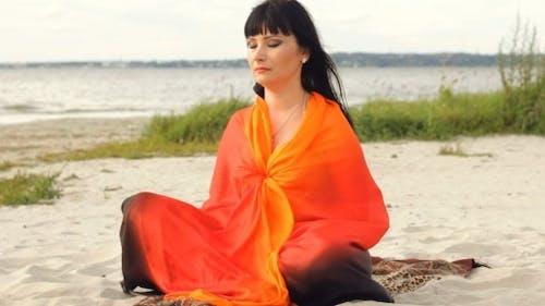 Young Woman Meditating By the Sea Long Shot