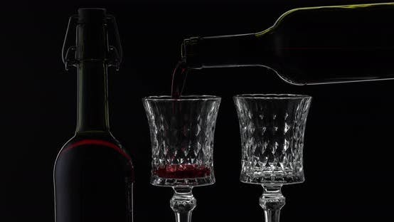 Rose Wine. Red Wine Pour in Two Wine Glasses Over Black Background. Silhouette