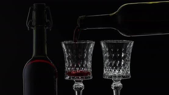 Roséwein. Rotwein gießen in zwei Weingläsern über schwarzem Hintergrund. Silhouette