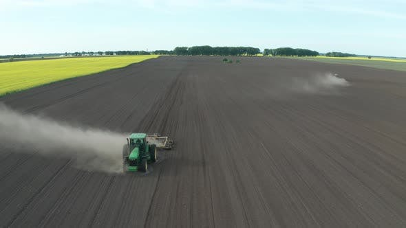 Thumbnail for Aerial Shot of Tractors Ploughing Soil for Seeding