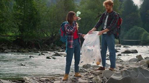 Volunteers Collecting Bottles in Bag