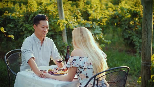 Cover Image for A Happy Asian Man Is Dining with a Beautiful Woman in an Elegant Summer Dress. Sit at a Table at the