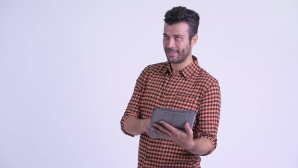 Cover Image for Happy Bearded Persian Hipster Man Thinking While Using Digital Tablet