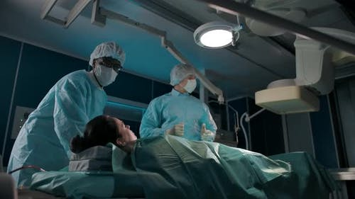 A Darkskinned Doctor Moves an Operating Table with Caucasian Female Patient