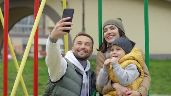 Thumbnail for Happy Young Couple and Child Taking Selfies on Playground