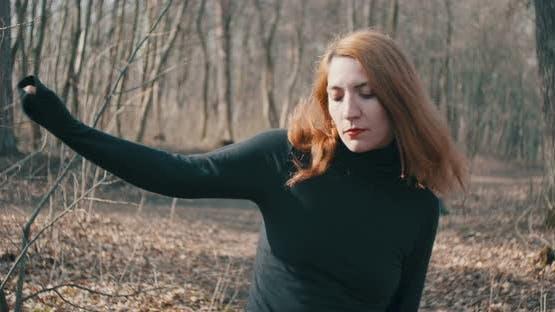 Rothaarige Frau tanzt im Wald