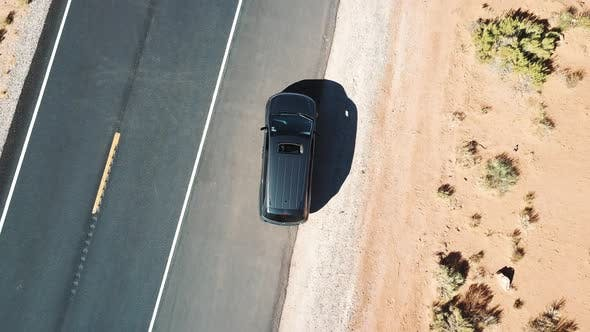 Thumbnail for Drone Quickly Rising Above Car with Sunroof Open Standing on Asphalt Road