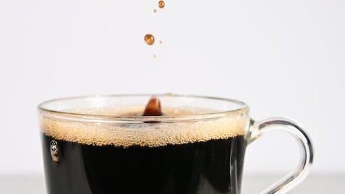 Werfen Würfel von braunem Zucker in transparentem Glas Tasse schwarzen Kaffee