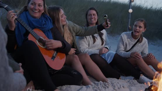 Thumbnail for Beautiful Group of Women Having Fun By the Beach Campfire at Dusk