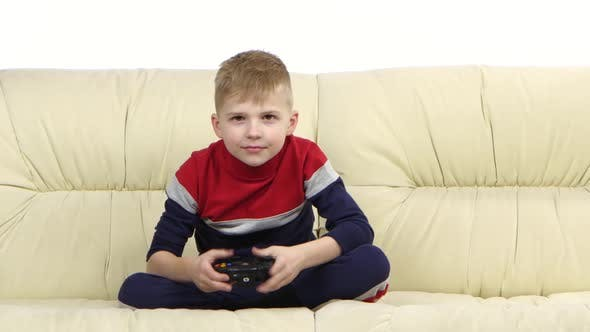 Little Boy with Games Console Playing Video Game on Couch