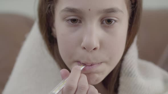 Thumbnail for Portrait of Teenage Girl Wrapped in a Blanket Takes a Thermometer in Her Mouth