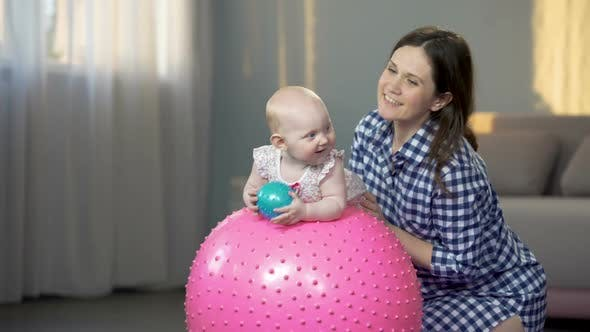 Thumbnail for Cheerful Mother Playing With Infant, Making Baby Fitness Exercises on Big Ball