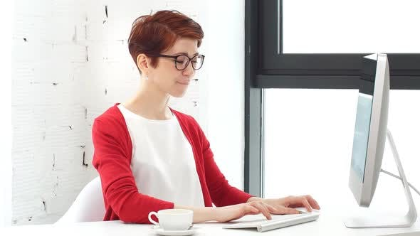 Thumbnail for Young Woman Working in Office, Sitting at Desk, Using Computer and Looking on Screen