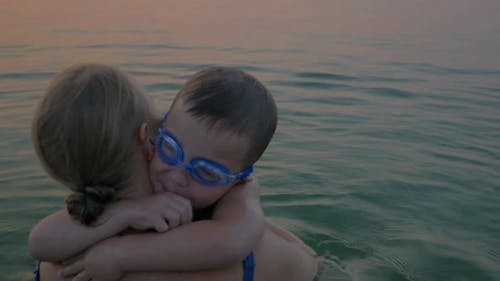 Hugs and kisses of mother with son in the sea