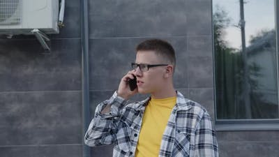 Young Man is Chatting with Friend on Phone
