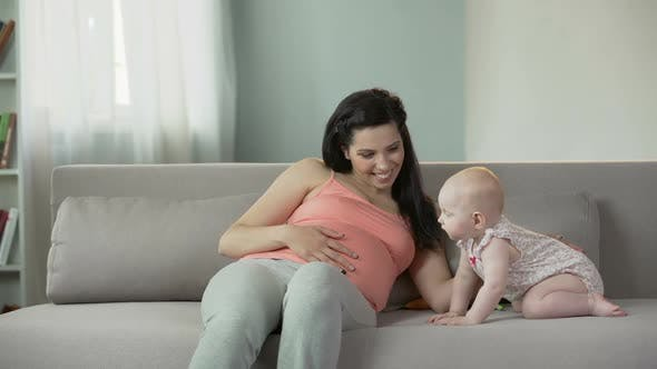 Beautiful Pregnant Woman Touching Belly Gently, Enjoying Time With Cute Baby