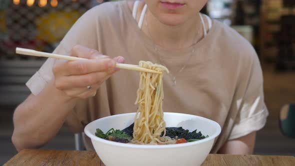 Hungry Girl Eating Noodles Out Her Ramen Soup with a Smile. Enjoying Healthy Organic Food