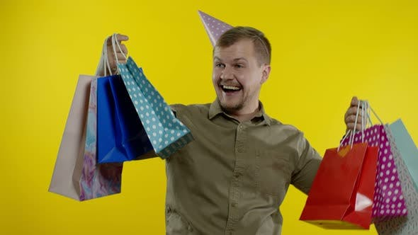 Man Raising Shopping Bags, Looking Satisfied with Purchase, Enjoying Discounts on Black Friday