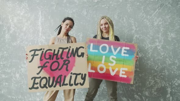 Female Lesbian Couple is Standing By the Wall with LGBT Posters