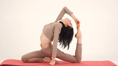 The Girl Practices Yoga on a Gymnastic Mat