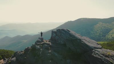 Hiker Stands on a Rock Looking to the Future at Sunset